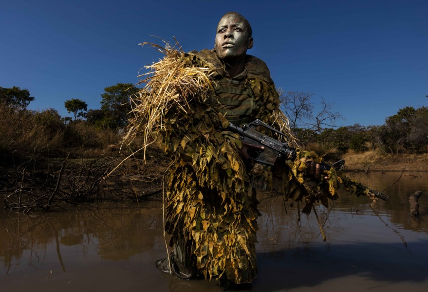 PHUNDUNDU WILDLIFE AREA, ZIMBABWE, JUNE 2018: Petronella Chigumbura, 30, an elite member of the all female conservation ranger force known as Akashinga undergoes sniper movement and concealment training in the bush near their base. Akashinga (meaning the 'Brave Ones' in local dialect) is a community-driven conservation model, empowering disadvantaged women to restore and manage a network of wilderness areas as an alternative to trophy hunting. Many current western-conceived solutions to conserve wilderness areas struggle to gain traction across the African continent. Predominately male forces are hampered by ongoing corruption, nepotism, drunkenness, aggressiveness towards local communities and a sense of entitlement. The I.A.P.F, the International Anti-Poaching Foundation led by former Australian Special Forces soldier Damien Mander, was created as a direct action conservation organisation to be used as a surgical instrument in targeting wildlife crime. In 2017 they decided to innovate, using an all- female team to manage an entire nature reserve in Zimbabwe. The program builds an alternative approach to the militarized paradigm of 'fortress conservation' which defends colonial boundaries between nature and humans. While still trained to deal with any situation they may face, the team has a community-driven interpersonal focus, working with rather than against the local population for the long-term benefits of their own communities and nature.
